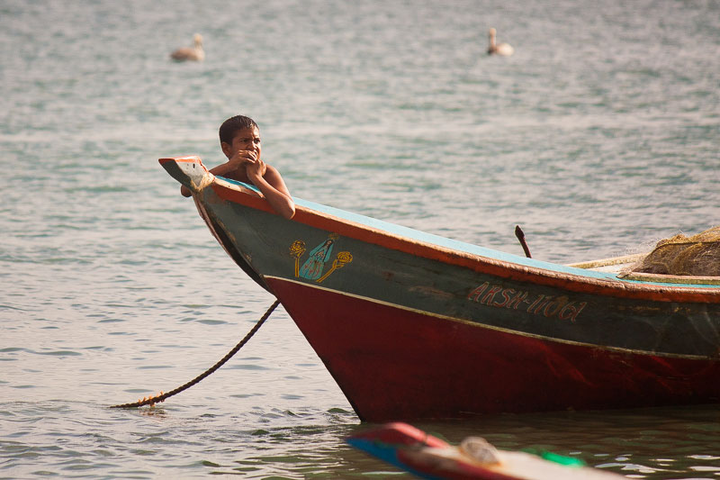 Kid in a fisherman's boat in Pampatar, Margarita Island, Venezuela